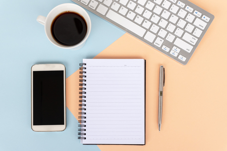 Directly above view of office desk with computer keyboard, cup of coffee,smart phone, note pad and pen on dual tones background