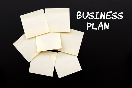 Business Plan text on black board with yellow stocky notes