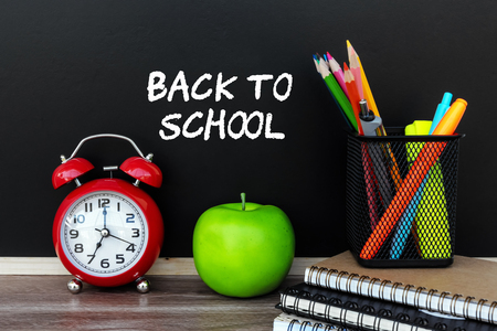 Back To School Text on Black Board with stationary, alarm clock and apple