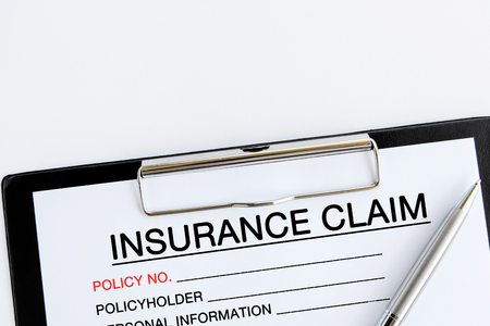 Insurance Claim Form on attached on Clip board and pen on white background