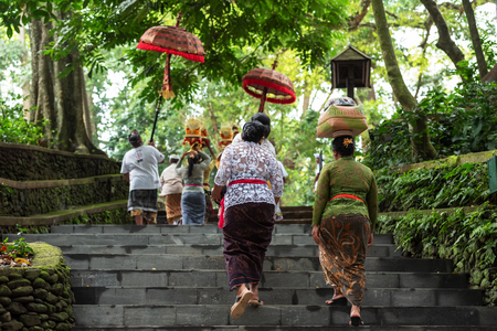 Ubud, Indonesia - April 04, 2019: Balinese parade with women carrying offering for Hindu God in Ubud Monkey Forest Temple