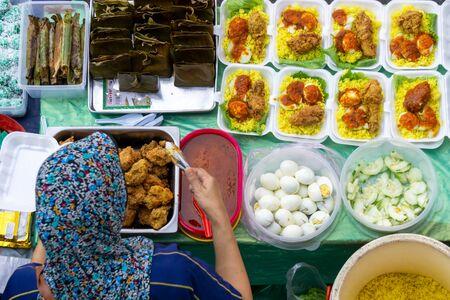Draufsicht des nicht identifizierten Anbieters, der gelbes Reispaket an der Garküche im Lebensmittelmarkt der Stadt Kota Kinabalu zubereitet Standard-Bild