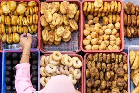 Top view of unidentified vendor and customer at the food stall in Kota Kinabalu city food market. Stock Photo
