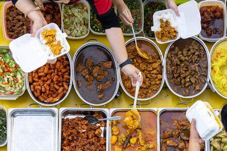 Buying food at the buffet stall in Kota Kinabalu market, Sabah, Malaysia.