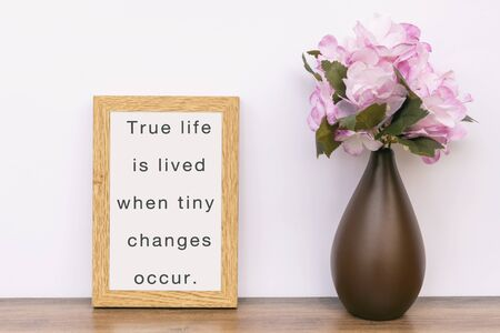 True life is lived when tiny changes occur - Inspiration quotes on wooden frame.