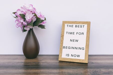 The Best time for new beginning is now - Inspiration quotes on wooden frame. Фото со стока