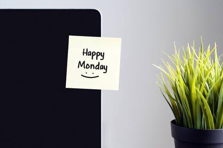 Happy Monday text on sticky note on laptop.