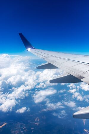 Clouds and airplane wing seen from window