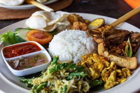 Nasi Campur Bali Bebek Betutu traduce arroz de pato mixto balinés, cocina balinesa de Indonesia.