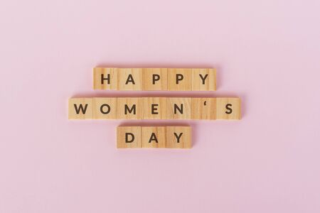 Happy Women's text on wood blocks. Pink background.