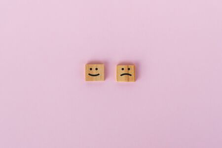 Sad and smiling symbol on wooden block, pink background.