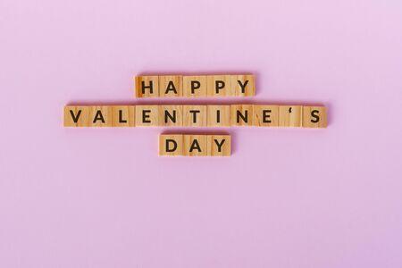 Happy Valentine's Day text wood blocks. Pink background.