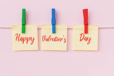 Happy Valentine's Day text on hanging paper note. Pink background. Imagens