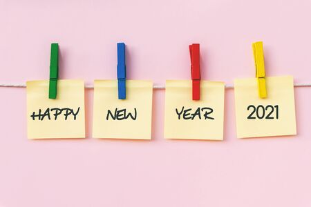 Happy New year 2021 greeting on hanging paper note, pink background. New Year concept.