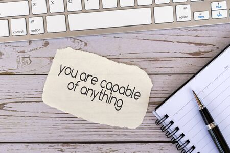 You are capable of anything inspirational quotes on torn paper on top of wood background