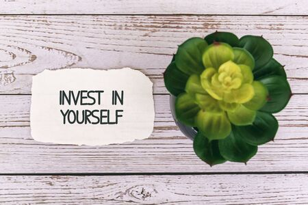 Invest in yourself inspirational quotes on torn paper on top of wood background
