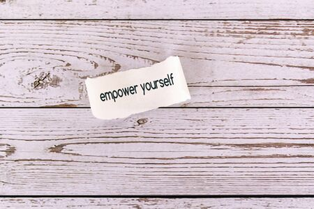 Empower yourself on a torn paper, wood background Imagens