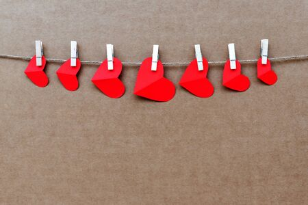 Valentine's day concept, red heart shape hanging on a rope brown background