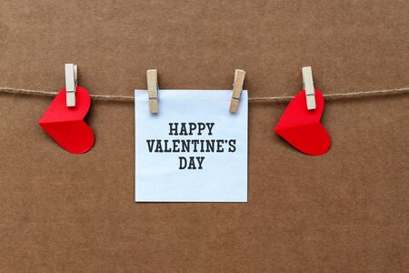 Happy Valentine's Day text on a paper note. Valentine's day concept, red heart shape hanging on a rope brown background Imagens