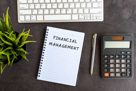Financial Management text on notepad on top of black textured background. Computer keyboard, pen, calculator and potted plant Imagens - 139892409