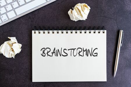 Brainstorming text on notepad on top of black textured background, computer keyboard, pen and crumpled paper ball Imagens