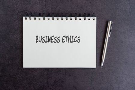 Business ethics text on notepad on top of black textured background Imagens