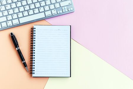 Notepad, pen, computer keyboard on top of pastel colored background