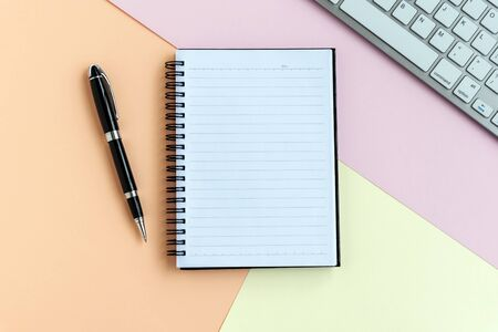 Notepad, pen, computer keyboard on top of pastel colored background Imagens - 139892413