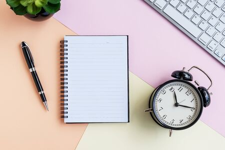 Alarm clock, Note pad, computer keyboard, green potted plant and pen on pastel colored background