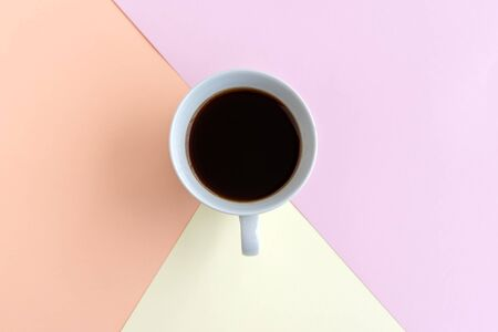 Cup of coffee on pastel background, pink yellow and beige color Imagens