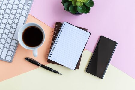 Note pad with cup of coffee, calculator, computer keyboard, potted plant and pen on colorful pastel colored background with copy space. Imagens - 139892414