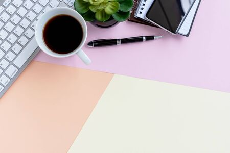 Note pad with cup of coffee, calculator, computer keyboard, potted plant and pen on colorful pastel colored background with copy space.