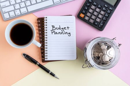 Budget Planning text on note pad with cup of coffee, calculator, computer keyboard, coin jar and pen on colorful pastel colored background