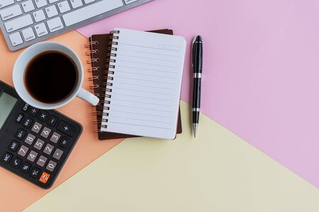 Note pad, cup of coffee, calculator, computer keyboard and pen on colorful pastel colored background