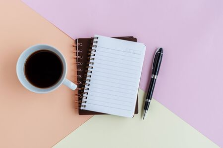 Note pad, cup of coffee and pen on colorful pastel colored background