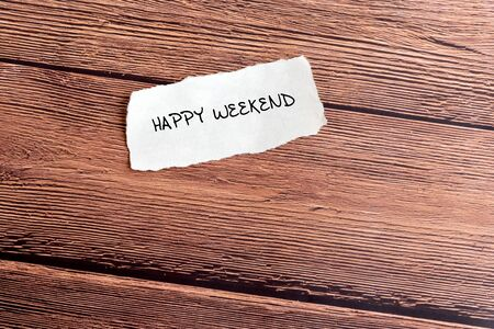Happy Weekend text on torn paper on top of wooden background.
