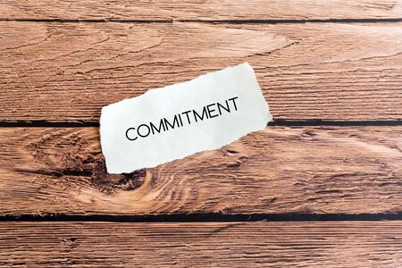 Commitment text on torn paper on top of wooden background.