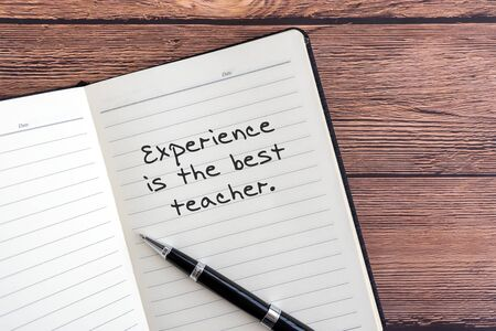Inspirational quotes - Experience is the best teacher. Notepad wooden background. Imagens