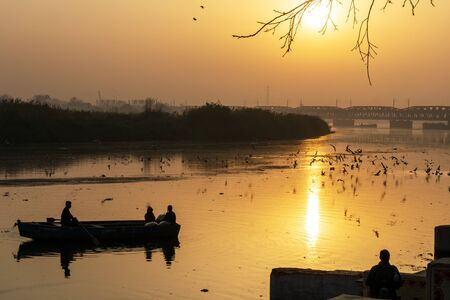 Tranquil sunrise view with a boat at Yamuna river in New Delhi India