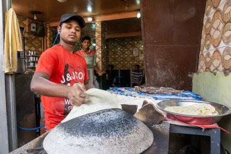Old Delhi, India - March 4, 2018: Unidentified Man baking an chapati roti at Chandni Chowk in Old Delhi India