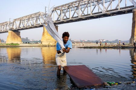 Uttar Pradesh, India - March 03, 2018: Unidentified man doing a laundry at Dhobi Ghat is a well known open air laundromat in Yamuna River, Agra. Imagens - 140919549
