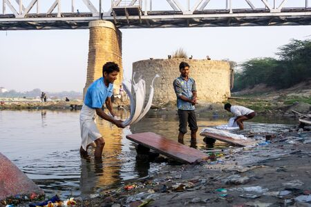 Uttar Pradesh, India - March 03, 2018: Unidentified man doing a laundry at Dhobi Ghat is a well known open air laundromat in Yamuna River, Agra. Imagens - 140919551