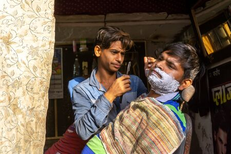 New Delhi, India - March 03, 2018: Unidentified man shaving a beard at Barber shop. Imagens - 140919552