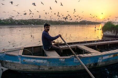 New Delhi, India - March 04, 2018: A man paddling a boat during sunrise at Yamuna river ghat in New Deli, India. Imagens - 140919556
