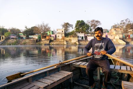 New Delhi, India - March 04, 2018: A man paddling a boat during sunrise at Yamuna river ghat in New Deli, India. Imagens - 140919559