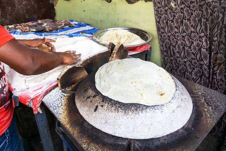 Man Preparing and cooking chapati roti at Chandni Chowk in Old Delhi India Imagens