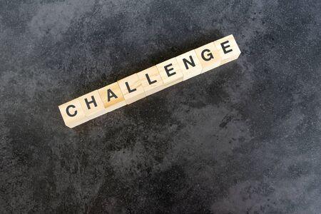 Challenge text on wooden block on black texture background