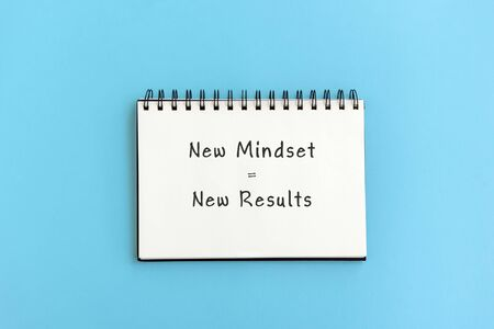 New mindset = New result text on notepad on blue background.