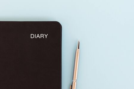 Black diary and pen on blue background with copy space. Imagens - 139892427