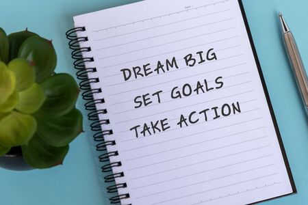 Inspirational quotes text on note pad - Dream big, Set goals, Take action.
